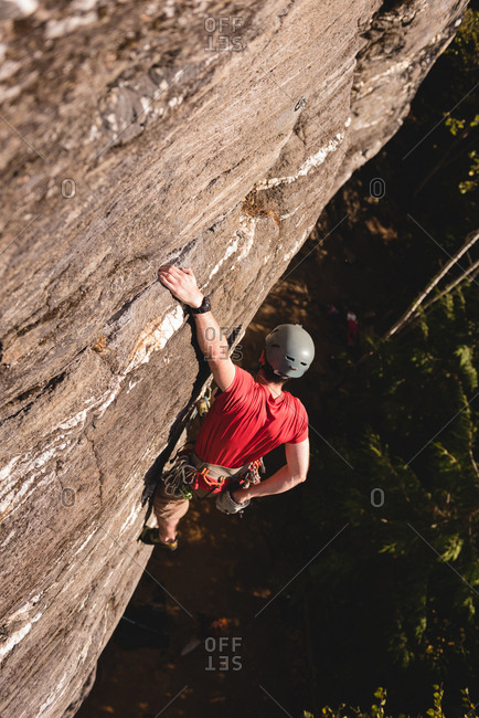 Rock climber climbing the rocky cliff in the forest