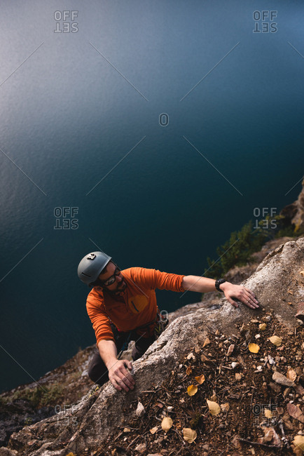 Rock climber reaching on the cliff top on a sunny day