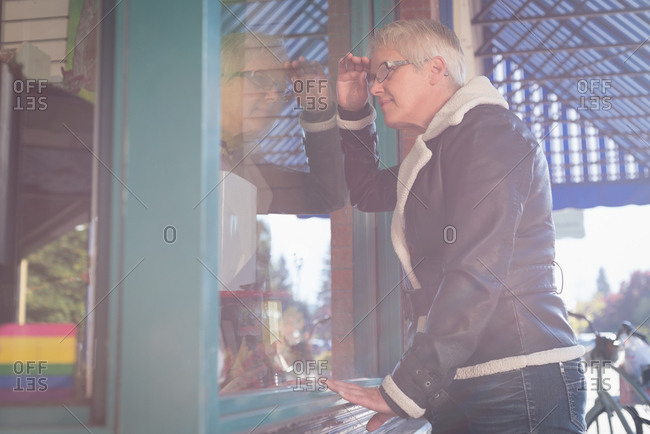 Senior woman peeping through the glass window outside the book store