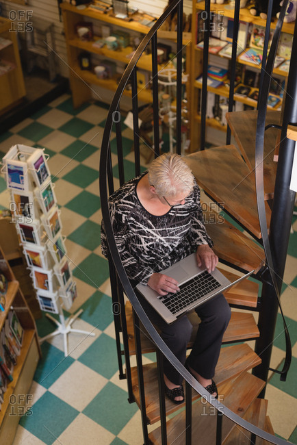 Senior woman using laptop in antique book store