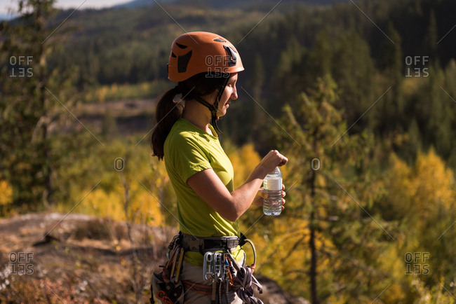 Side view of thirsty female climber drinking water
