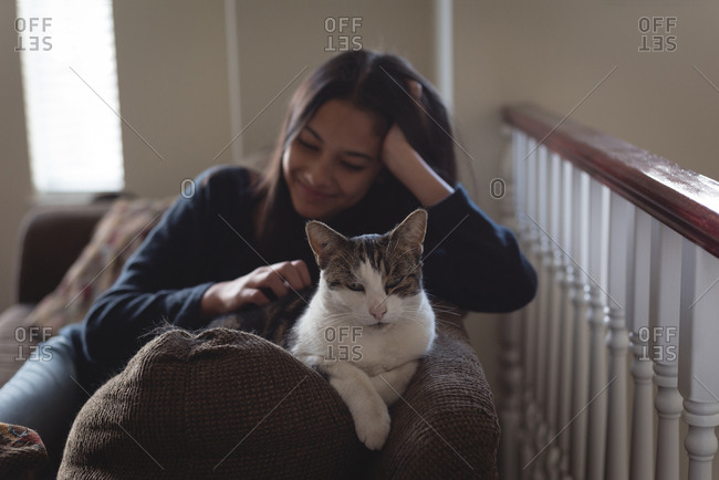 Teenage girl sitting with cat on sofa in living room at home