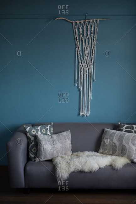 Thread curtain hanging against blue wall in living room