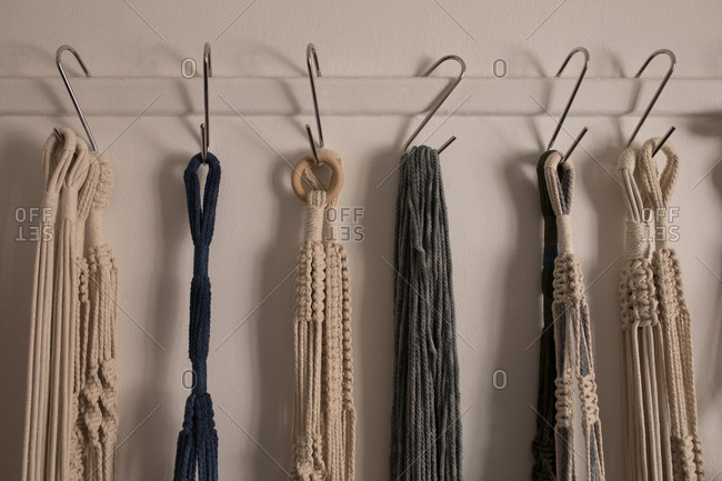 Various dyed thread on hook against wall