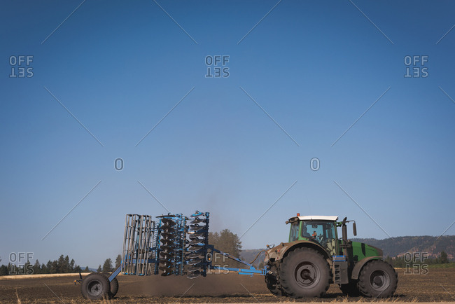 Tractor sprinkling fertilizer in field on a sunny day