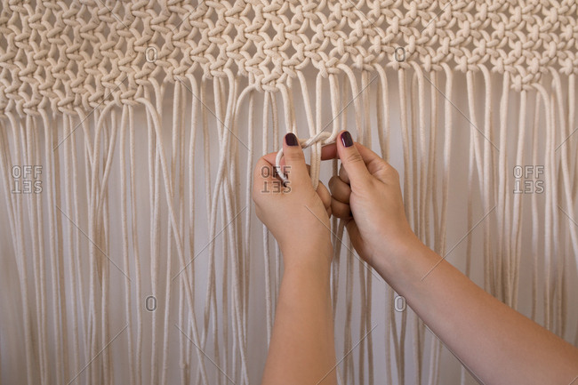 Woman knotting strings against wall