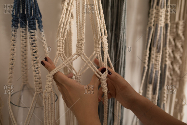 Woman knotting strings in workshop