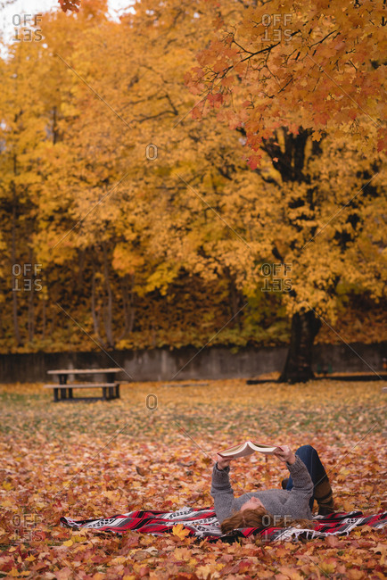 Woman lying down in the park and reading novel during autumn