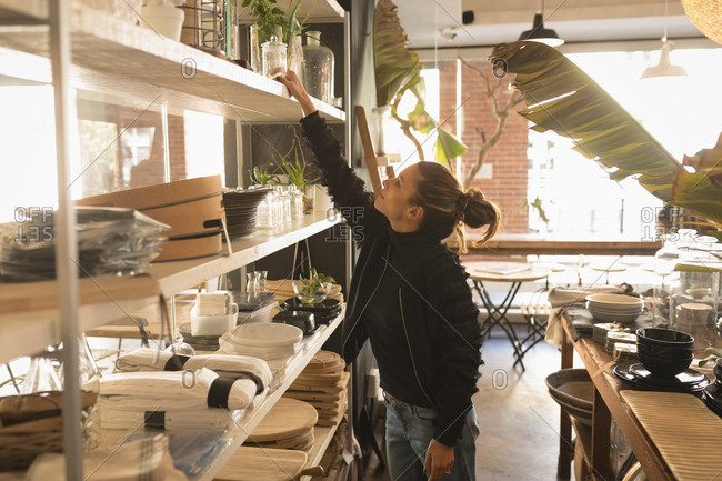 Woman placing a jar in shelf in shelf at coffee shop