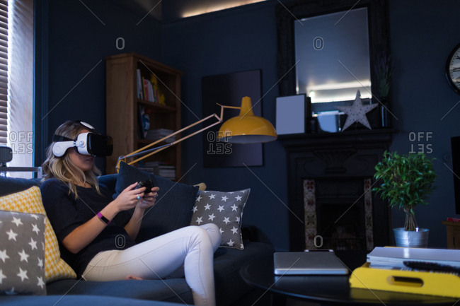 Woman sitting on sofa and using her virtual reality headset at home