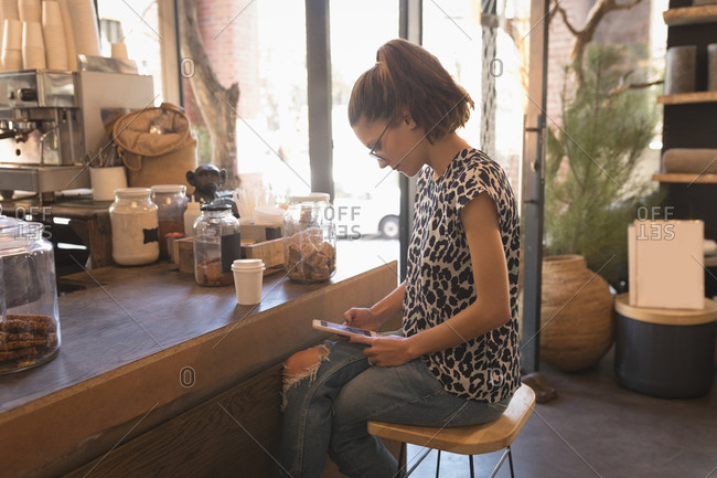 Woman using digital tablet at counter in coffee shop