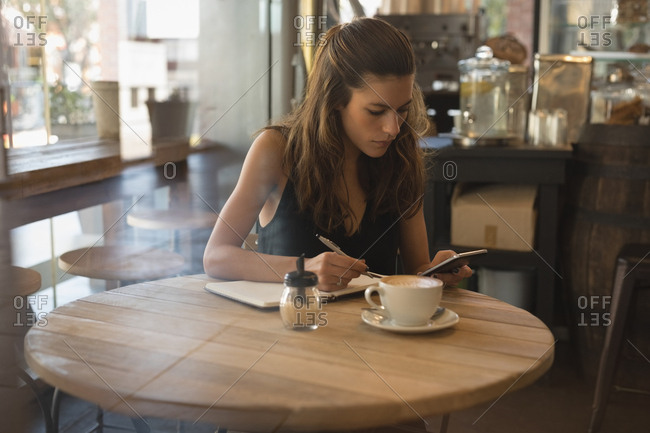 Woman using mobile phone while writing on diary in coffee shop
