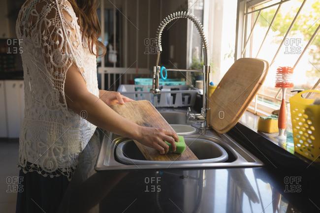 Woman washing cutting board in sink at kitchen