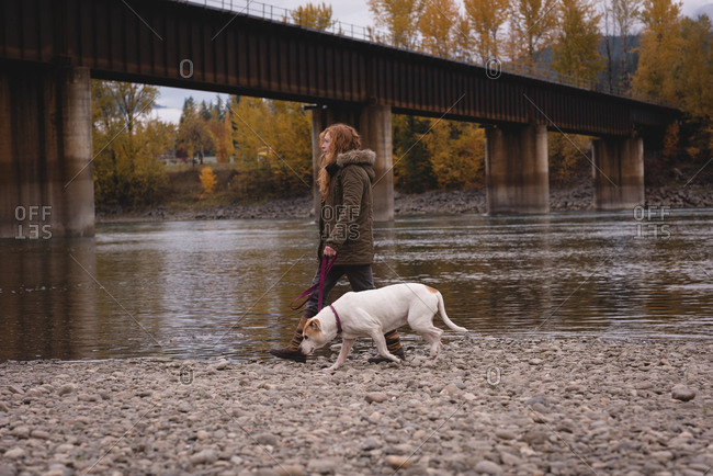 Woman with her pet dog walking by the river during autumn