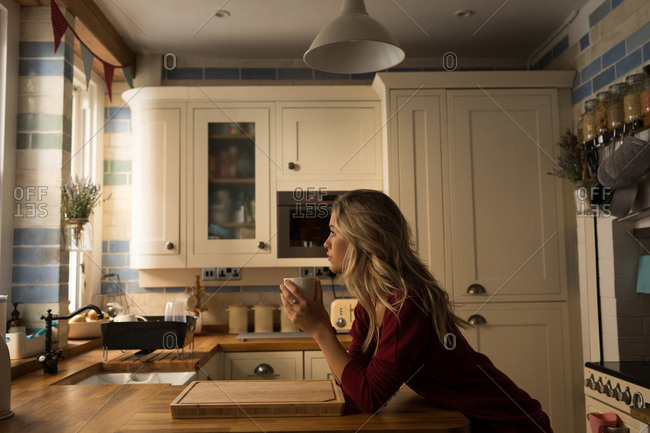 Young woman leaning on kitchen counter having coffee at kitchen