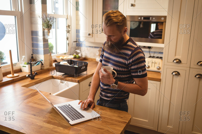 Man having coffee while using a laptop