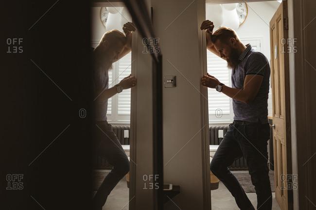 Depressed man lining on wall