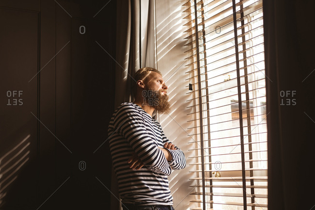 Thoughtful man watching out from the window