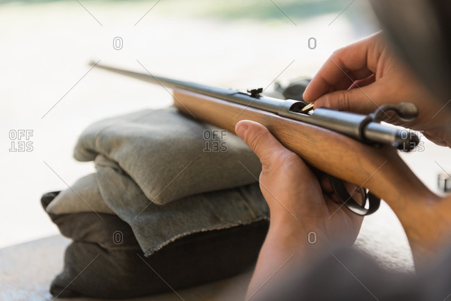 Man loading bullet into shotgun