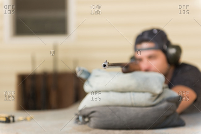 Man aiming sniper rifle at target in shooting range