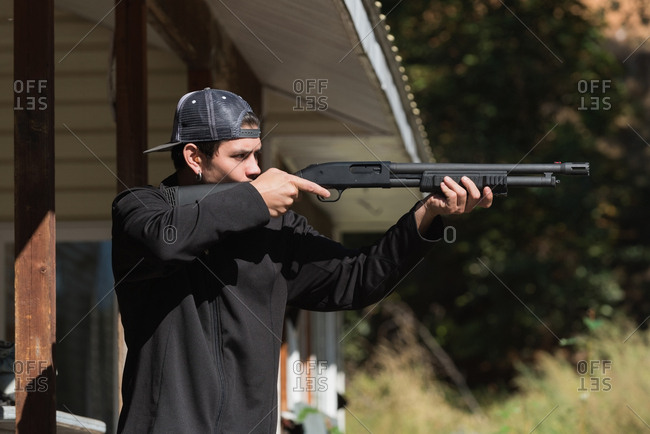 Man aiming shotgun at target in shooting range