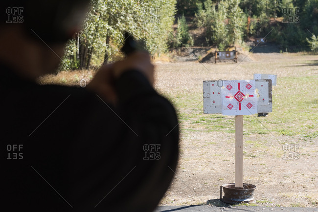 Man aiming gun at target in shooting range