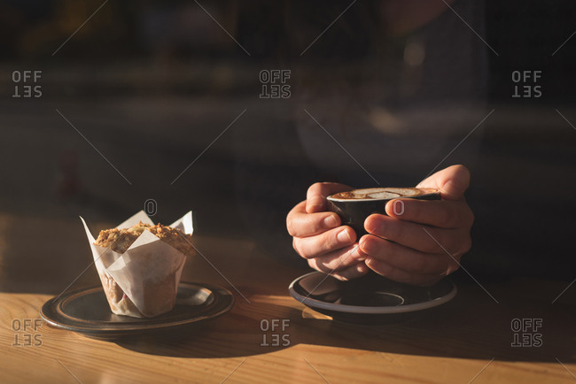 Mid section of woman having coffee and breakfast