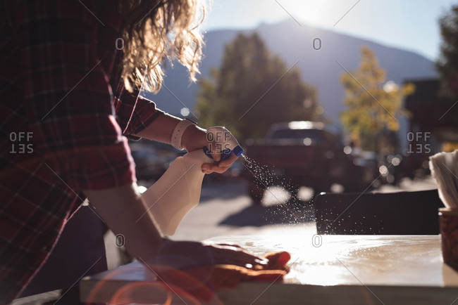 Woman spraying water while cleaning table