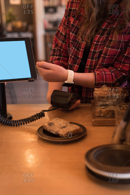 Customer making payment with smartwatch at counter