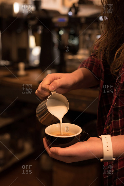 Mid section of female barista preparing coffee at counter