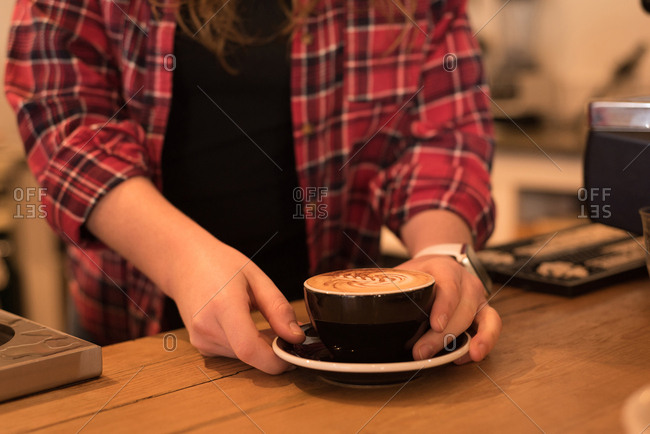 Mid section of female barista serving coffee at counter