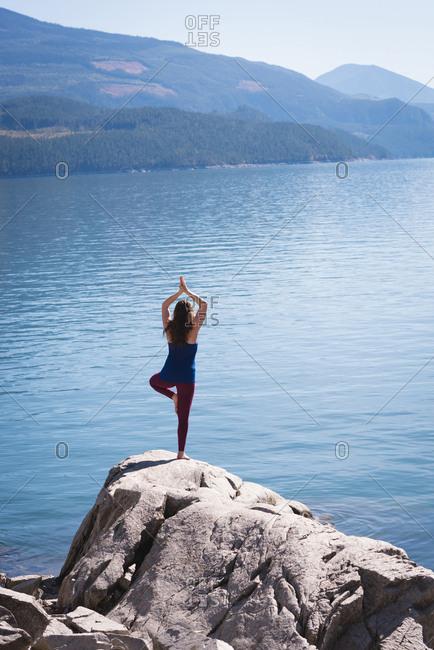Woman practicing yoga on rock