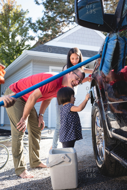 Father and kids having fun while washing car