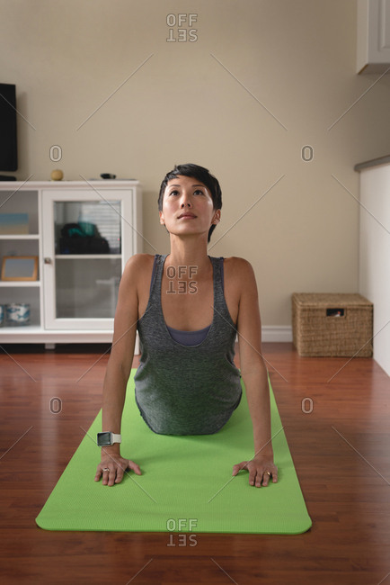 Woman performing yoga in living room
