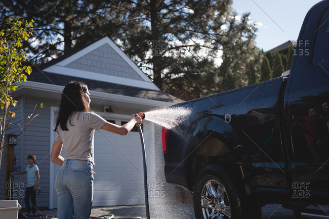 Woman washing her car with a high pressure water jet