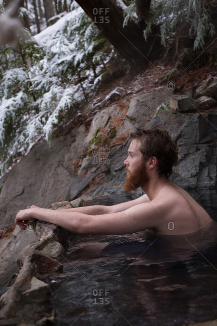 Thoughtful man relaxing in hot spring