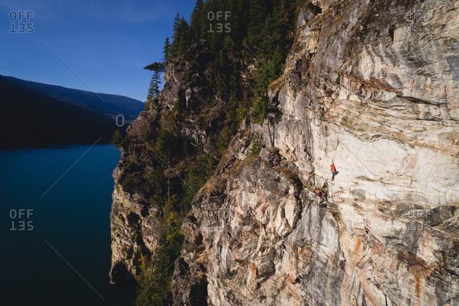 Rock climber climbing the cliff near the sea