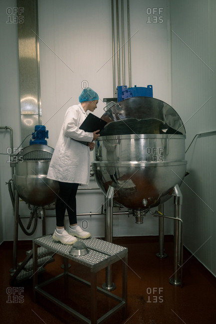 Female worker inspecting the food production line