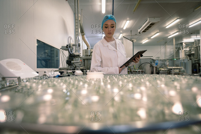 Female worker monitoring the glass jars on the production line