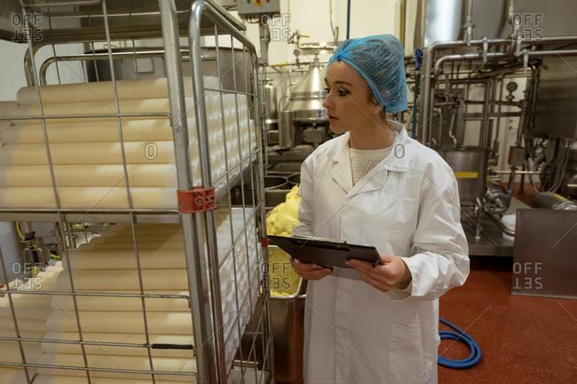 Female worker monitoring the food rolls kept in shelf