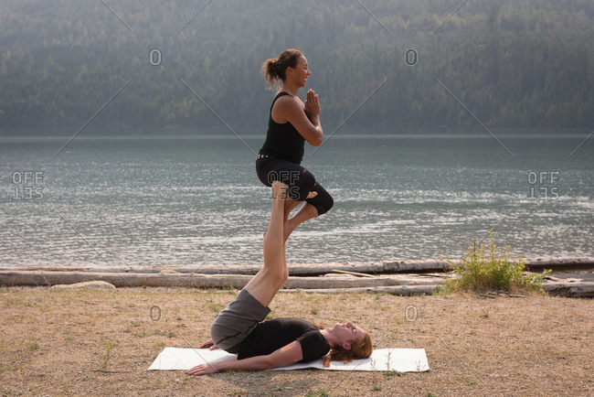 Sporty women practicing acro yoga on an open ground