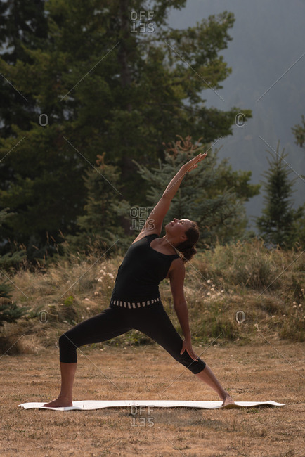 Fit woman performing stretching exercise on an open ground