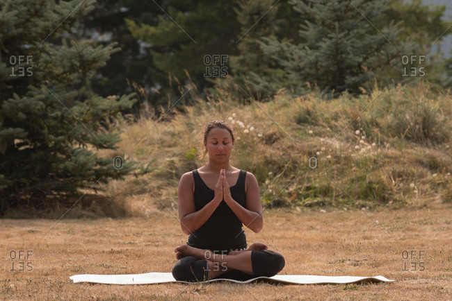 Fit woman sitting in meditating posture on an open ground