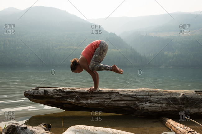 Fit woman performing a hand stand on a fallen tree trunk