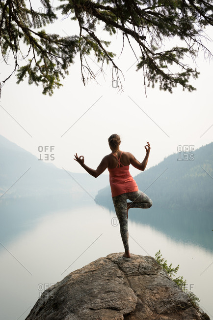 Fit woman balancing on one leg on the edge of a rock