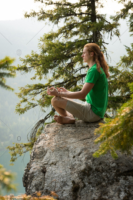 Fit man sitting in meditating posture on the edge of a rock