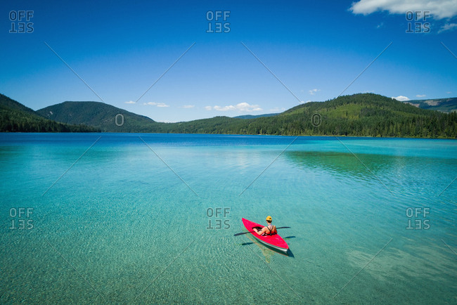 Kayaker kayaking in shallow turquoise water