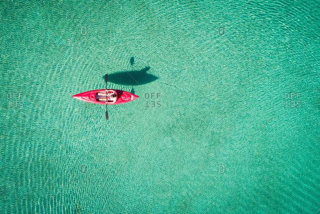 Kayaker kayaking in shallow turquoise water
