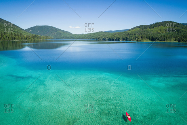 Kayaker kayaking in shallow turquoise water along the coastline
