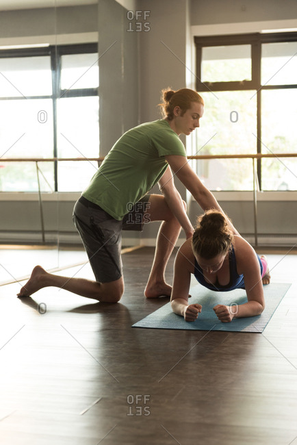 Trainer assisting woman in practicing yoga